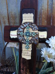 "Reclaimed wood cross with Amazing Grace sheet music. 1st layer of wood has a rust/ brown patina. 2nd layer of wood was left in its natural aged patina and has a 4"" iron ""G"" for the 1st letter of ""grace"". 6 Swarovski Rhinestones were added to compliment the gem stones on the metal cross, giving it a further vintage look. This is a beautiful cross honoring faith in Christ."