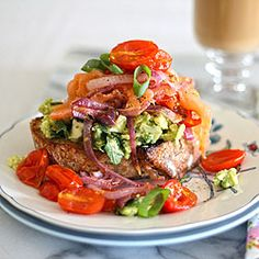 A decadent, colorful breakfast sandwich with feta, avocado, roast tomato and smoked salmon on sourdough