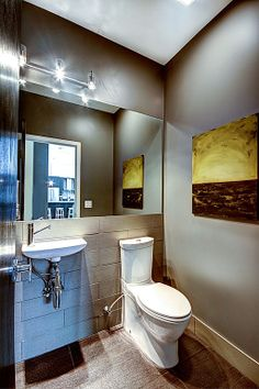 Modern Powder Room - Find more amazing designs on Zillow Digs!  Patty likes this toiletto.  Large mirror.  Lights are ouchy, tho.