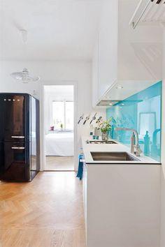 white cabinets; turquoise backsplash, wooden floor, black SMEG fridge