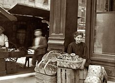 "Lena Lochiavo: Cincinnati, August 1908. ""Lena Lochiavo, 11 years old, 209 West Sixth Street. Basket [and pretzel] seller at Sixth Street Market in front of saloon entrance."" Photograph and caption by Lewis Wickes Hine."