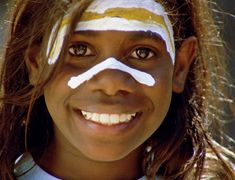 An Aboriginal girl continuing with her heritage by painting her face for a ritual. The viewer can see the happiness in the participation of her culture, which in some ways in unknown to the rest of the world.