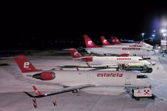 Boeing 737 and Bombardier CRJ freighters lined up at night. Estafeta USA offers air cargo express freight services for companies wishing to ship products to customers in Mexico.