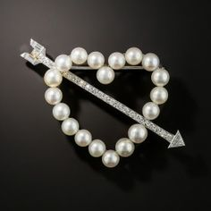 Cupid strikes again! This time with lustrous white pearls and a sparkling diamond-set arrow all set in gleaming platinum. 2 inches from arrowhead to fletching. Mid-20th-century vintage.