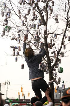 A man climbs a tree to hang another Pabst Blue Ribbon beer can during the 55th St. Patrick's Day Parade from a loft on Michigan Ave in Corktown, Detroit's historic Irish neighborhood, Sunday March 10, 2013.