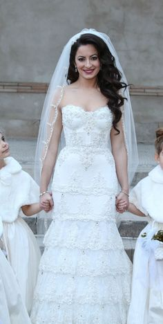 This is a detailed, romantic, beautiful dress that can only be purchased through Kleinfelds in New York. This dress is a Pnina Tornai Exclusive. It has crystals and beads that hang off each tier that