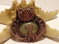 Prehnite pendant in oxidized copper. Back. Made by Gedő Mária.