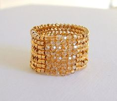 This is a wide beaded band ring woven of 18kt Gold Plated Delica Beads and Golden Shadow Swarovski Crystals. This ring really makes a statement and