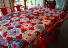 red Grandmother's flower garden quilt, rescued/repaired and used as a table cloth, at 13th street studio