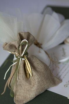 Προσκλητήριο και μπομπονιέρες με μεταλλικά διακοσμητικά σε σχήμα ελιάς.