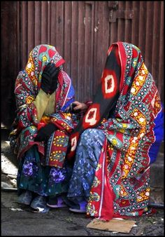 Yemen | Women draped in vivid 'sitarahs' with the tie-dyed face masks or 'maghmuq' | ©Anne Dowd & Len Phillips ~ from their Arabian Encounter Portfolio