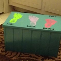 Target foot stool spray painted. Used acrylic paint to make kids footprints and then added. Ames and year with paint pen.