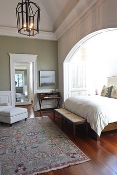 houzz.com: This subtly masculine bedroom features a king bed with upholstered headboard and wooden rails and footboard. The bed is flanked by custom bedside tables with bow fronts and a lower cane shelf. A luxurious duvet covers the bed with accent pillows that pick up on the wall color and rug colors.