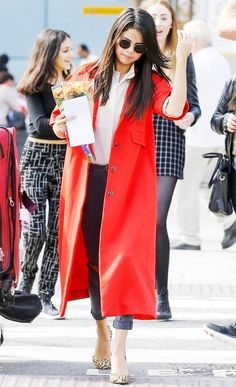 Selena Gomez in a vibrant red coat, white button up top tucked into ripped grey denim, and leopard slingback pumps.