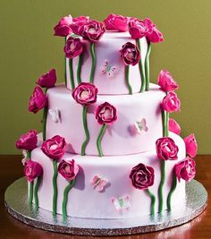 Pink flowers climbing up a three tiered cake with butterfly accents