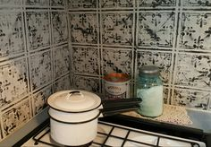 After reconstructing the damaged walls behind the stove, we painted tin ceiling panels and nailed as a backsplash.