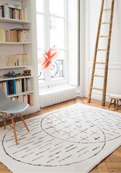 Whitespace and lots of light; ladder and vertical bookshelves to emphasize height and space. Rug+Masomenos