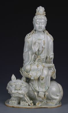 China, Yuan Dynasty, Ying Qing Guanyin, in seated position, seated on a mythical animal figure, holding up one had, with detailed robes and necklace, has minor repair. Height 13 1/4 in.