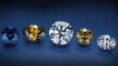 A representative selection of colored and colorless synthetic diamonds grown by the General Electric Company in the 1970s. The largest faceted stone in the center weighs 0.78 carats. Photo by Robert Weldon. GIA. (041013)