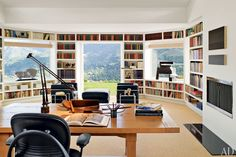 Interior designer Sally Sirkin Lewis lined a graceless bay in a 1980s house in Carmel Valley, California, with shelves to create a grand modern library. The central window was knocked out and French doors were introduced to connect the renovated room with the mountainous landscape (2005).