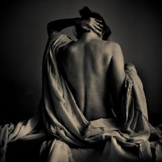 The chiaroscuro lighting in this photo dramatizes the image and makes the muscles in her back stand out. The lighting gives it a much more dramatic feel and creates deep shadows within the fabric.