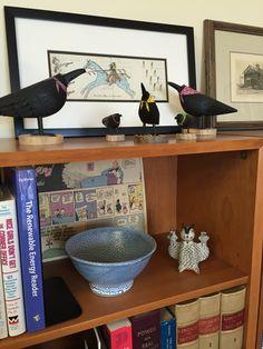 Folk art crows, ledger art and pottery adorn an office bookshelf.