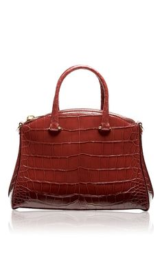 This Trevi 32 top handle bag by **VBH** is rendered in rich cranberry crocodile skin and features the designers classic rounded arch and gold-tone hardware. Exuding ladylike elegance, it is a covetable accessory that will never go out of style.