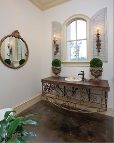 Powder Room has a repurposed iron railing console.  Notice the indoor shutters with applied sconces.