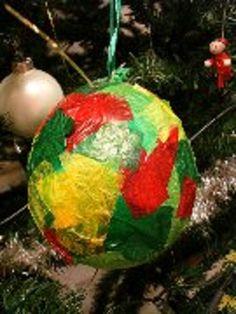* Kerstbal: Blaas de ballon een klein stukje op. Plak het vliegerpapier met verschillende kleuren op de ballon. Laat de ballon goed drogen. Maak een lintje aan de ballon om het in de kerstboom te hangen.