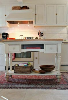 """A kitchen island created from a sofa table. In addition to a butcher block top, she used bun feet to add 6.5"""" more inches of height."""