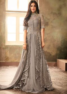 Grey colored flared twin layered gown style kameez in net with santoon lining underneath designed with heavy thread, zari and resham embroidery work all over enhanced by beautiful sequins and stone embellishment. Accompanied by a plain santoon bottom and a laced chiffon dupatta, both in matching grey color. Do Note: All accessories shown are for styling purpose only. Slight color variation may occur due to photographic reasons. The semi-stitched kameez can be customised up to 42 inches.
