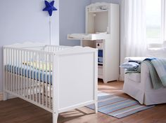 Ein Kinderzimmer mit HENSVIK Babybett in Weiß mit 3-teiligem SOVDAGS Babybett-Set in Blau, LEKANDE Tagesdecke in Blau/Grün und SUNDVIK Wickeltisch/Schrank in Weiß