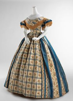 Evening dress  date: 1857-1860 Victoria wore tartan or plaids to honor Scottish. The textiles were the combination of fibers ex. Barege. The female silhouette of the middle of the 19th century consisted of a fitted corseted bodice and wide full skirts.
