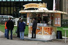 A small crêperie-  Serving crêpes as a form of fast food or street food, or may be a more formal sit-down restaurant or café.   Crêperies are typical of Brittany in France; however, crêperies can be found throughout France and in many other countries.   Because a crêpe may be served as both a main meal or a dessert, crêperies may be  may offer other baked goods such as baguettes. They may also serve coffee, tea, buttermilk and cider (a popular drink to accompany crêpes).