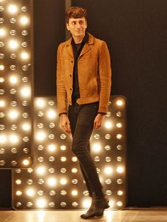 Hedi Slimane wears a black collared shirt, suede jacket, skinny jeans, and black boots