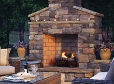 Outdoor covered patio with stone fireplace and chair for Modular outdoor fireplace