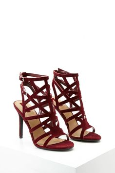 A pair of faux suede heels featuring a laser-cut caged design, open toe and back, and adjustable buckled ankle straps.