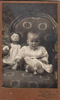 Vintage photo of a baby and her ragdoll, circa 1900.