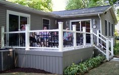 A beautiful Timbertech composite deck with white Radiance railing. Notice the Deckorator pickets accented with Deckorator baskets. Notice how the color of the deck blends perfectly with the home. Patio Deck Designs, Yard Design, Deck Skirting, Deck Colors, Front Deck, House Deck, Decks And Porches, Front Porches, Deck Railings