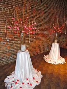 Pedestals made of skinny tables draped with puddling satin and rose petals and arrangement on top with sparkly strings hanging down.