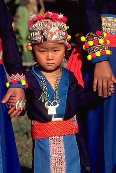 White Hmong girl in her finery. Holding her parent's hands, a White Hmong girl in northern Thailand wears her finest clothes and silver jewelry. | © John Spies