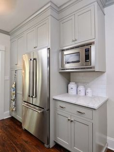 Benjamin Moore Fieldstone paired with gray kitchen cabinet crown moldings with marble countertops and white subway tile backsplash. Gray shaker kitchen cabinets above stainless steel double door counter-depth refrigerator and built-in microwave nook. Grey Kitchen Cabinets, Kitchen Cabinet Design, Kitchen Cabinet Crown Molding, Grey Kitchen, Painted Kitchen Cabinets Colors, Grey Shaker Kitchen, Studio Kitchen, White Subway Tile Backsplash, Kitchen Design