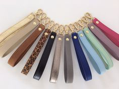 Very Important!!!!!!!!! This listing is only for the leather wrist strap. All other items shown are simply for display purposes. These gorgeous leather wrist straps are available in 12 colors for you to choose from. It is made with leather on both sides giving it a more luxurious look and long lasting.  Available in gold and silver finish.   Add to any bag with a ring, or on a zip puller to transform it to a practical wristlet clutch. Or simply attach it to your wallet or keys.  Also its the…