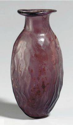 A ROMAN GLASS DATE FLASK CIRCA 1ST-2ND CENTURY A.D. Aubergine in color, mold-blown in the form of a date, with a short neck and out splayed mouth, the rim folded in 3 in. (7.6 cm.) high