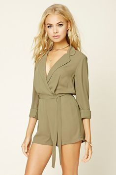A woven romper featuring a self-tie belt, a notched collar, a V-neckline, 3/4 cuffed sleeves, an elasticized waist, and front pleats.