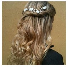 Fancy wavy hair half up/ half down hairstyle with flower hairpiece