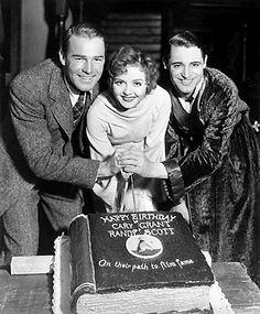 HAPPY BIRTHDAY - Nancy Carroll assists Randolph Scott and Cary Grant in the cutting of a cake to celebrate their birthdays