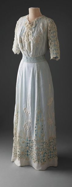 "Lingerie dress, 1910-13, Hillwood Estate, Museum & Gardens. One piece Edwardian lingerie dress of sheer lawn appropriate for warm summer wear. Open embroidery work embellishes the neck, sleeves, waist and skirt where vertical panels culminate in an elaborate 8"" horizontal band at hem. Embroidered iris motifs decorate the skirt panels and center bust. This transparent garment would have been worn with an undergarment which which could have contrasted in color..."