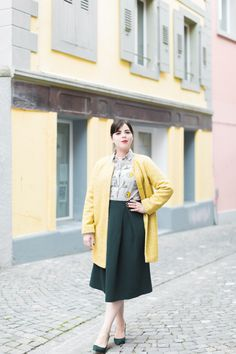 An outfit to make you smile: Pauline pairs a Boden classic shirt with the Maggie Ottoman Midi in green (glade green to be precise!). And brings the Boden sunshine with our Sienna Herringbone coat in yellow.  P.S. We don't paint walls, but if we did, they'd be just like the pastel ones behind Pauline.