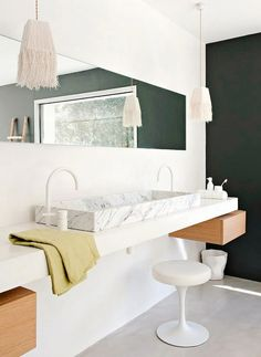 Fringed pendant lights Beautiful marble trough standalone sink handing from the wall keeps the space uncluttered and spacious.  Love the mirror that matches the shape of the sink.  White color palette and hanging pendants.